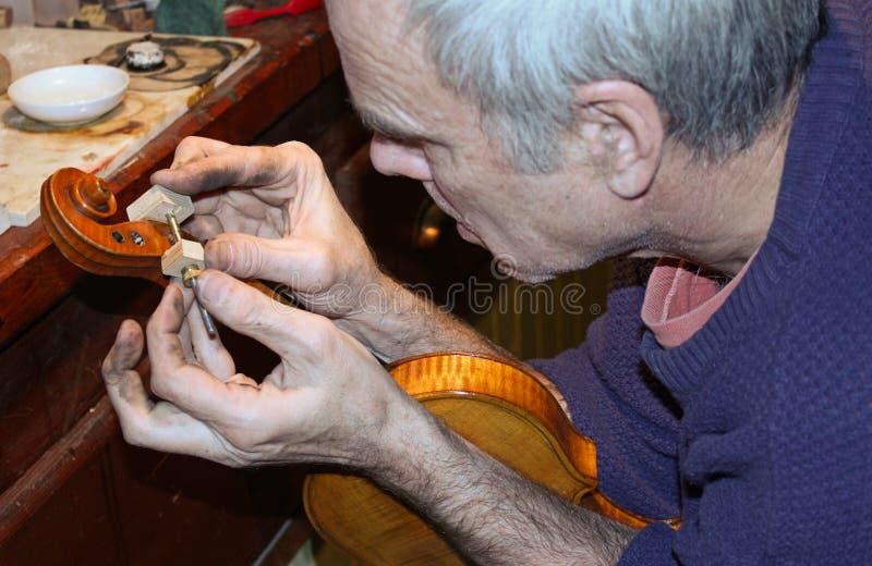 Uomo che lavora ad un violino fotografia stock