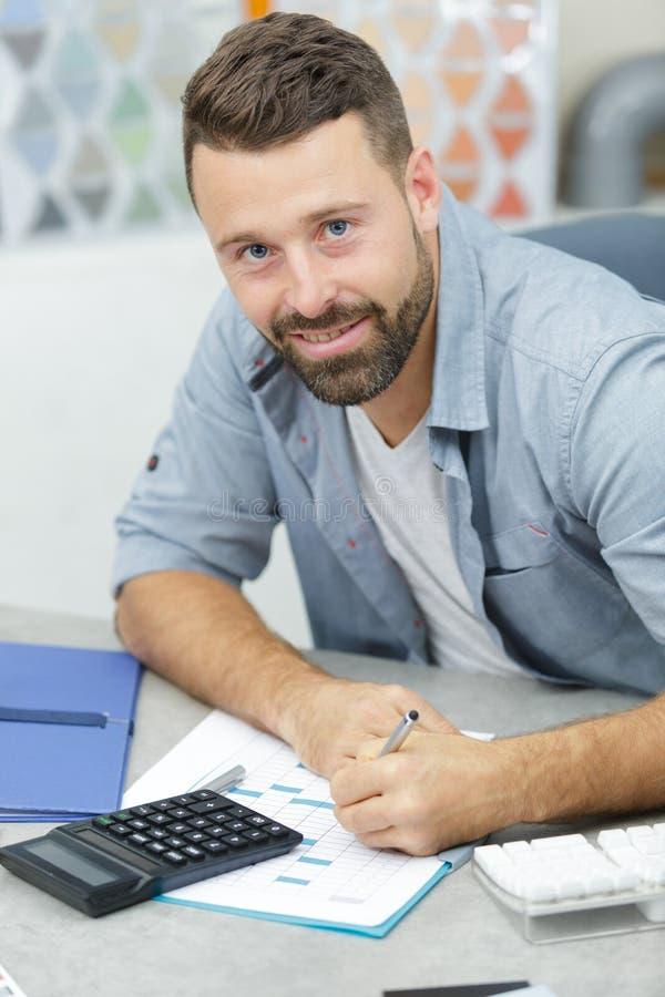 Uomo che lavora al disegno ed al calcolatore di ingegneria in ufficio fotografia stock