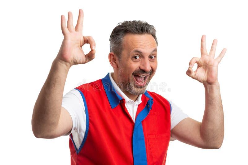 Uomo che lavora al supermercato che mostra doppio gesto di approvazione immagine stock libera da diritti