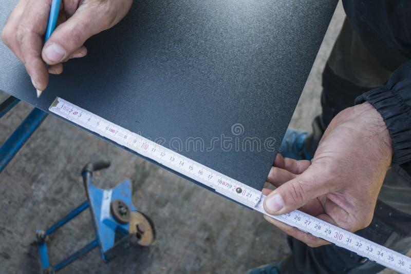 Uomo che lavora alla lamina di metallo del tetto nella costruzione del sito immagine stock