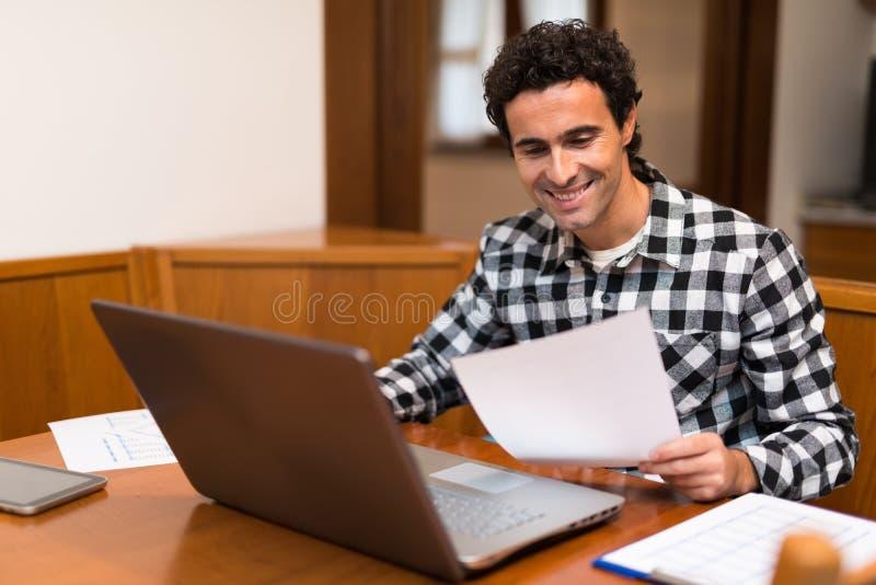 Uomo che lavora a casa con il suo computer portatile immagini stock libere da diritti