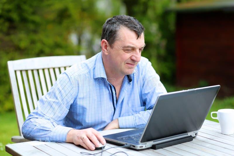 Uomo che lavora con il computer portatile a casa fotografia stock libera da diritti