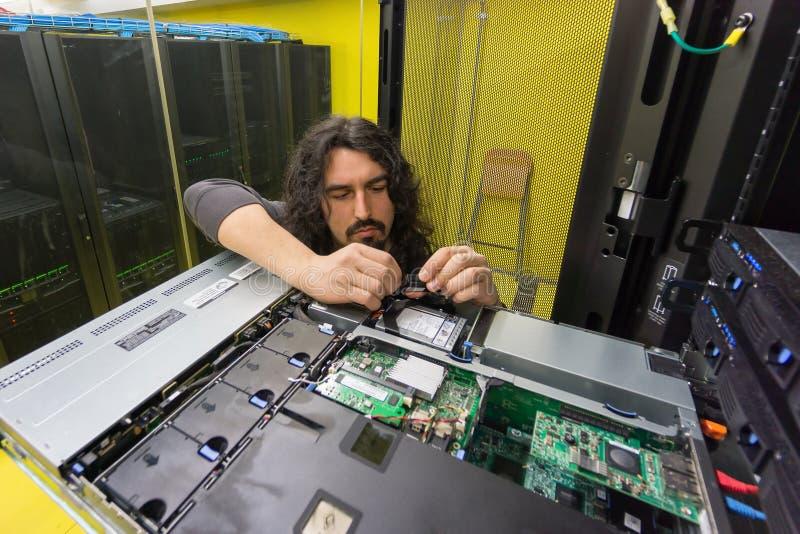 Uomo che lavora con il server nel centro dati immagine stock