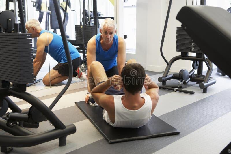 Uomo che lavora con l'istruttore personale In Gym immagini stock