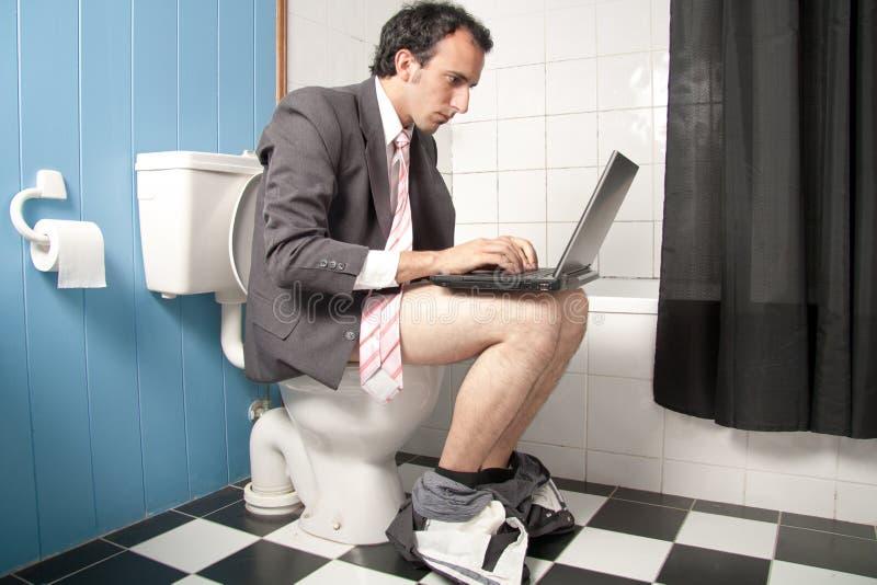 Uomo che lavora con un computer portatile in WC fotografia stock