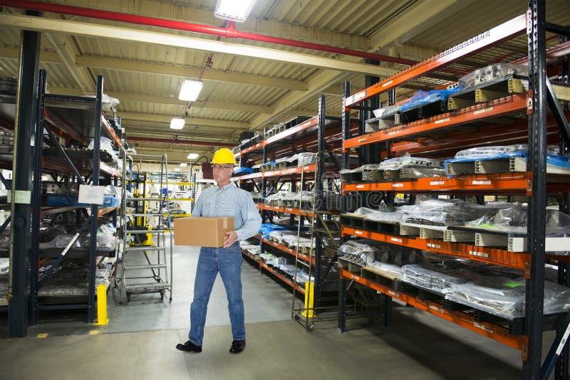 Uomo che lavora nel magazzino industriale di fabbricazione fotografie stock