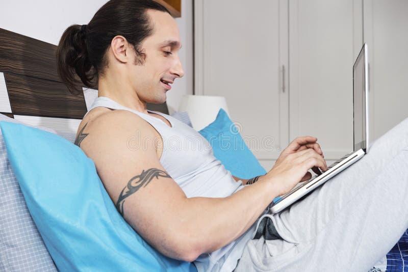 Uomo che lavora online a casa fotografia stock libera da diritti