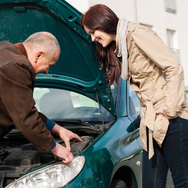 Uomo che lavora a riparare l'automobile della donna immagini stock