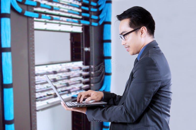Uomo che lavora vicino ai server di rete immagini stock