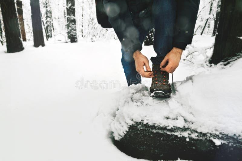 Uomo che lega stile di vita nevoso della foresta di inverno degli stivali dei laccetti fotografia stock