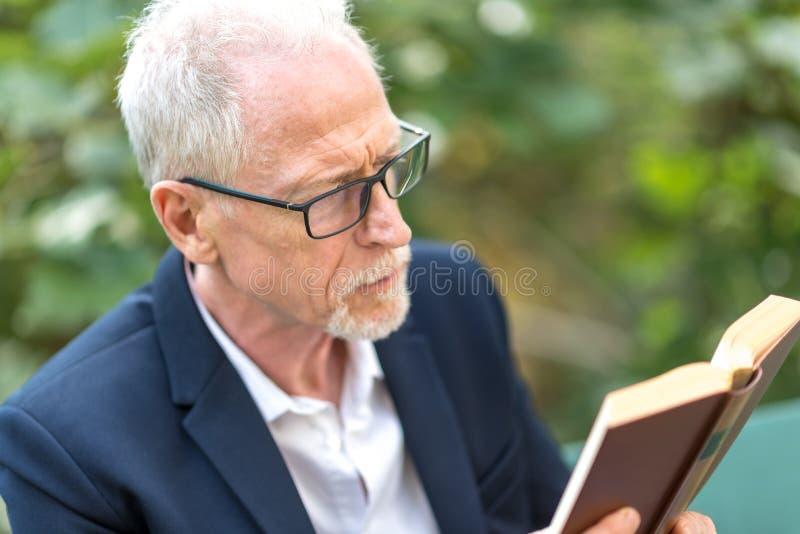 Uomo che legge un libro all'aperto immagine stock