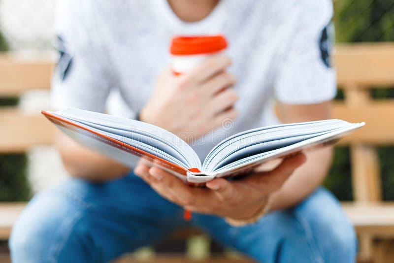 Uomo che legge un libro e che beve caffè Riposo del giovane immagine stock