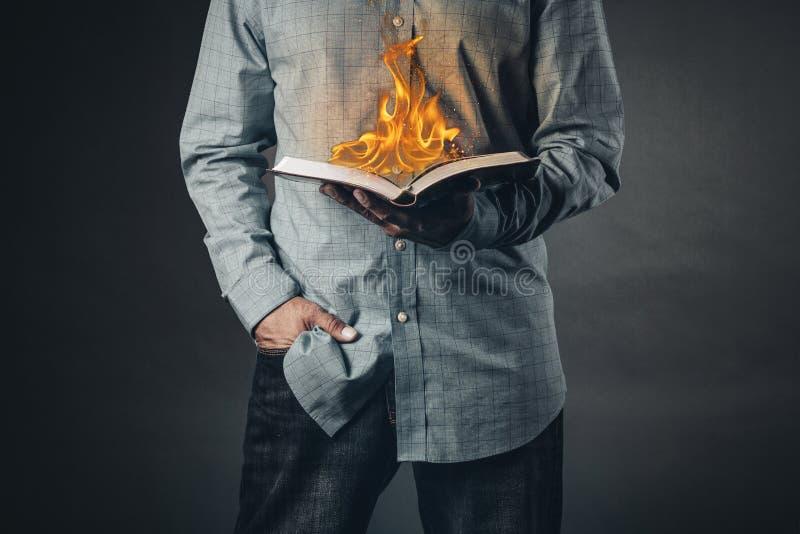 Uomo che legge un libro sul fuoco fotografia stock