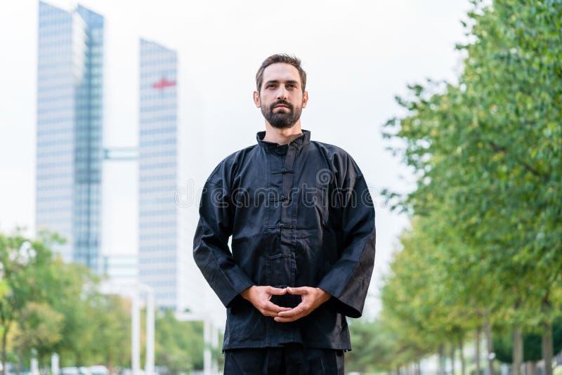 Uomo che medita facendo le arti marziali in città fotografia stock