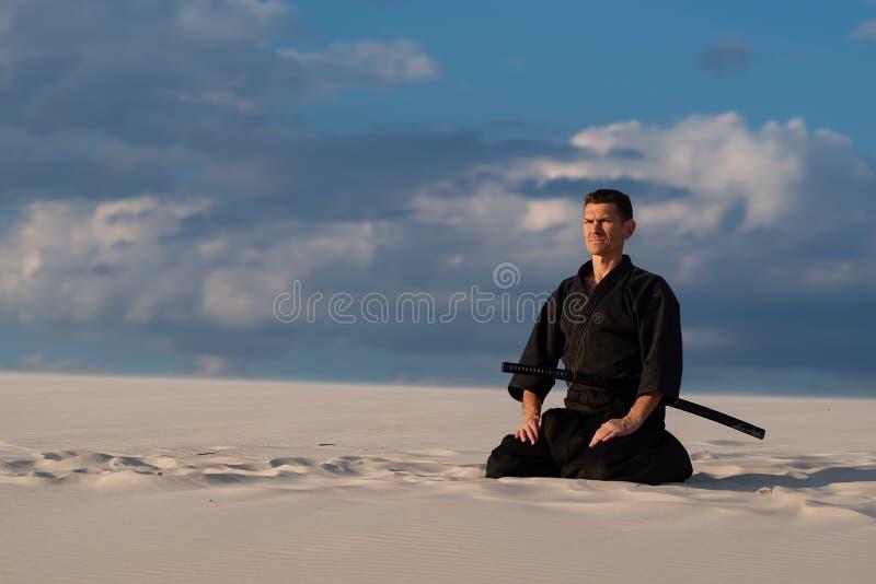 Uomo che medita prima della formazione di arti marziali fotografie stock libere da diritti