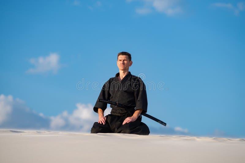 Uomo che medita prima della formazione di arti marziali fotografia stock