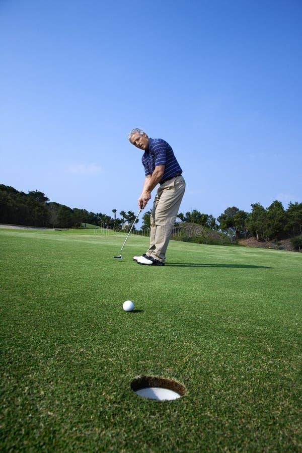 Uomo che mette al terreno da golf. fotografie stock