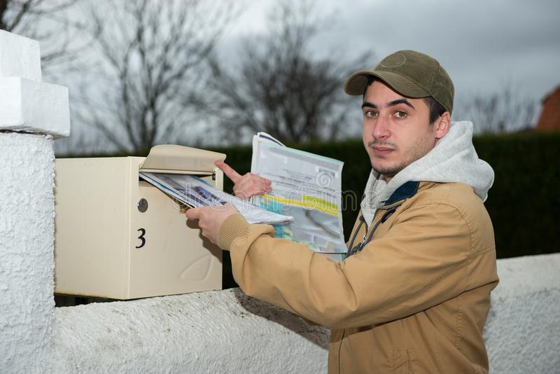 Uomo che mette giornale dalla cassetta delle lettere fotografie stock