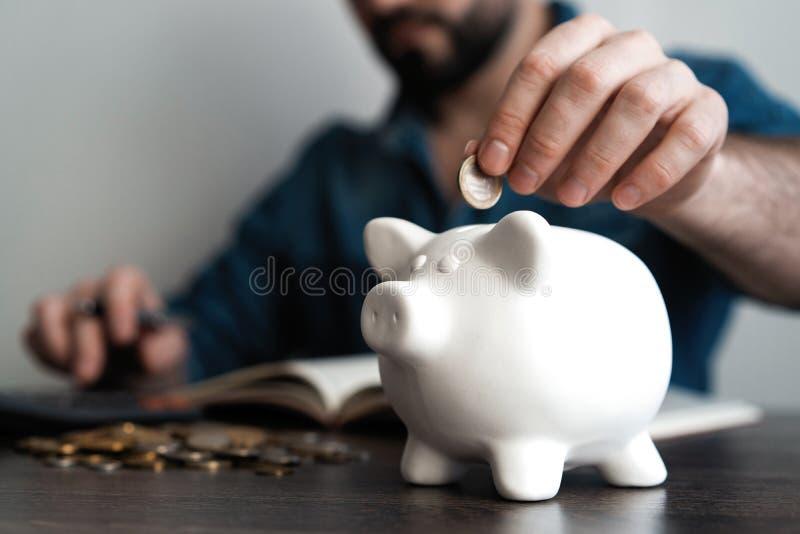 Uomo che mette moneta nella banca piggy Concetto dei soldi di risparmio immagini stock