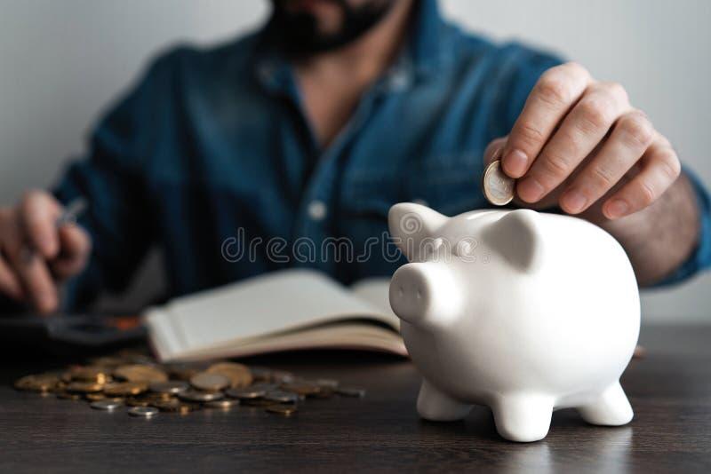 Uomo che mette moneta nella banca piggy Concetto dei soldi di risparmio fotografia stock libera da diritti