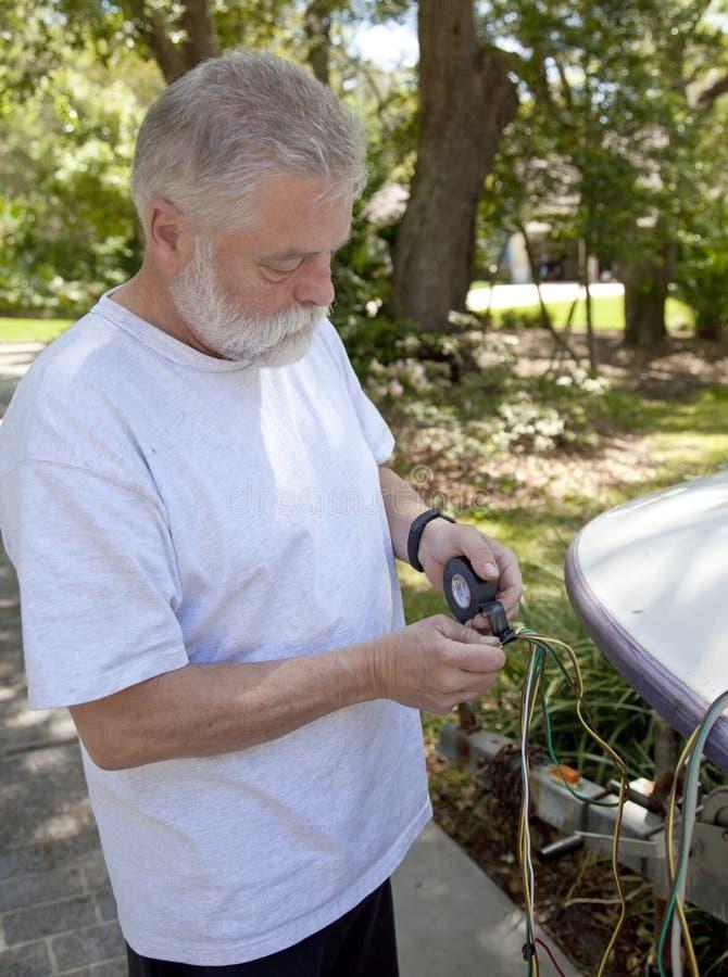 Uomo che mette nastro elettrico sui collegare immagine stock