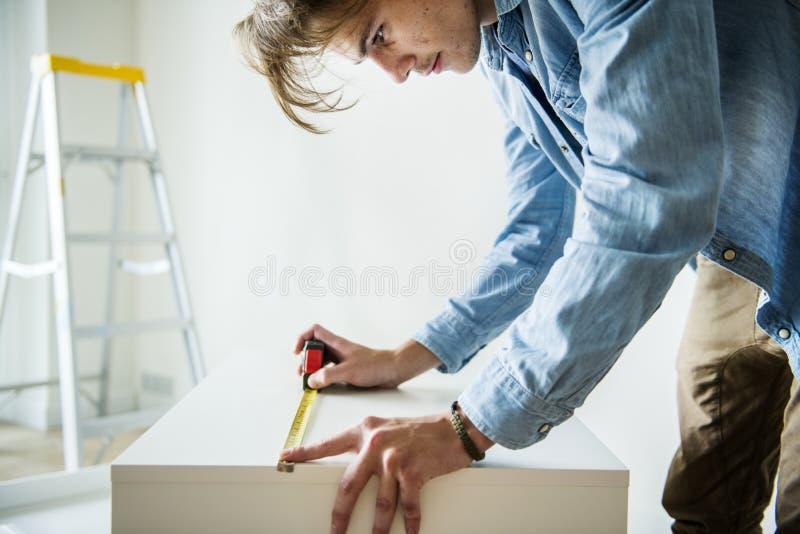 Uomo che misura il carpentiere del gabinetto fotografie stock