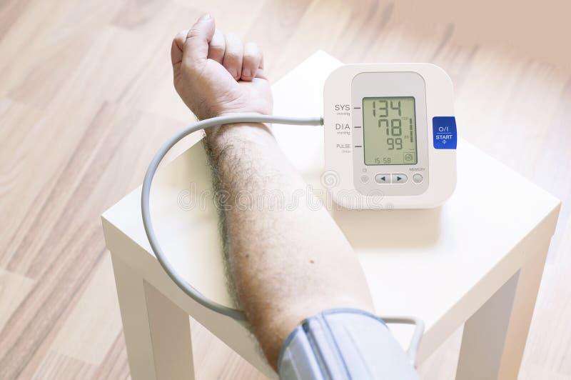 Uomo che misura la sua pressione sanguigna fotografia stock libera da diritti