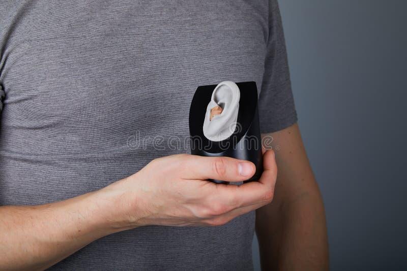 Uomo che mostra l'uso della protesi acustica fotografie stock