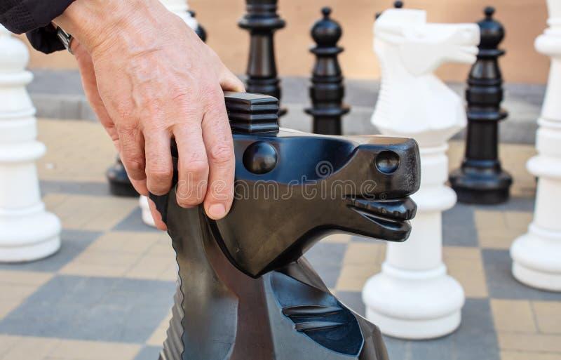 Uomo che muove il cavallo gigante del pezzo degli scacchi all'aperto immagini stock