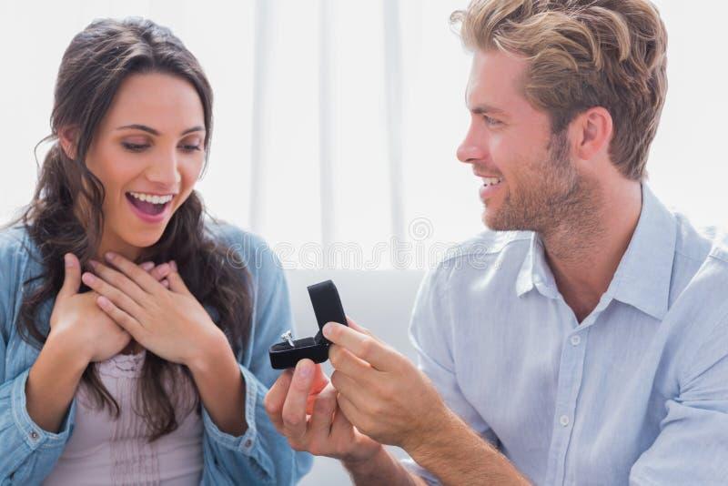 Uomo che offre un anello di fidanzamento al suo partner immagini stock libere da diritti