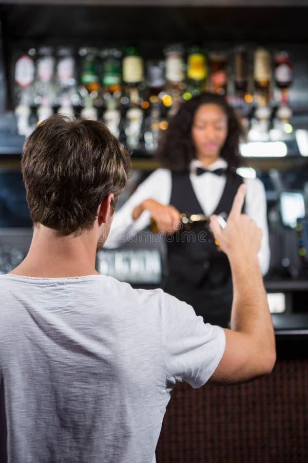 Uomo che ordina una bevanda al contatore della barra fotografia stock libera da diritti