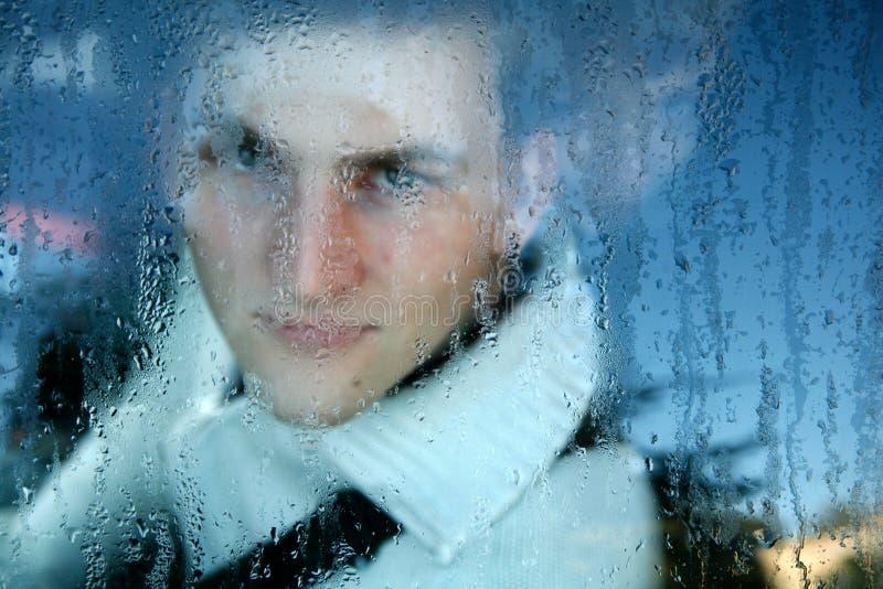 Uomo che osserva attraverso la finestra immagini stock