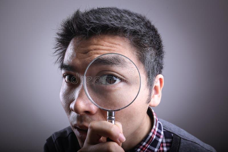 Uomo che osserva tramite una lente d'ingrandimento fotografia stock libera da diritti