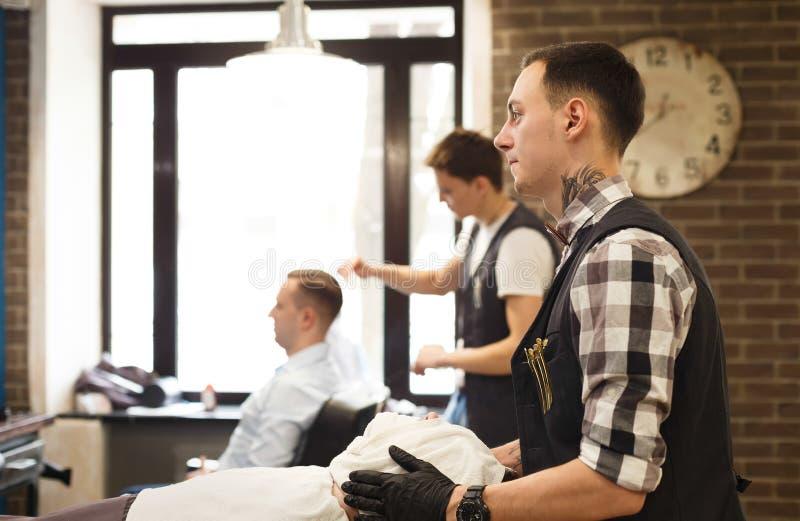 Uomo che ottiene taglio di capelli dal parrucchiere al parrucchiere immagini stock libere da diritti