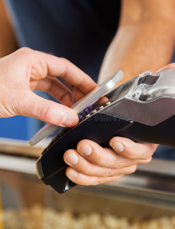 Uomo che paga con la tecnologia di NFC al cinema immagine stock libera da diritti