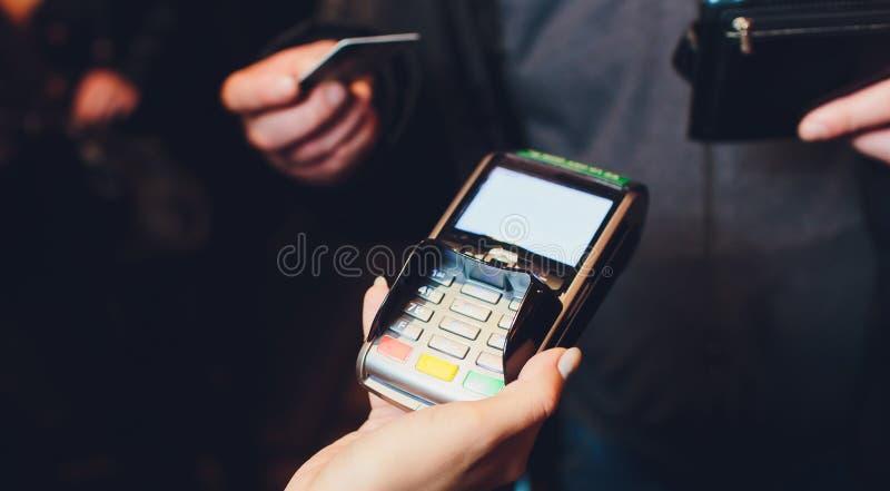Uomo che paga con la tecnologia di NFC sul telefono cellulare nel centro commerciale, punto di vista, primo piano fotografia stock libera da diritti
