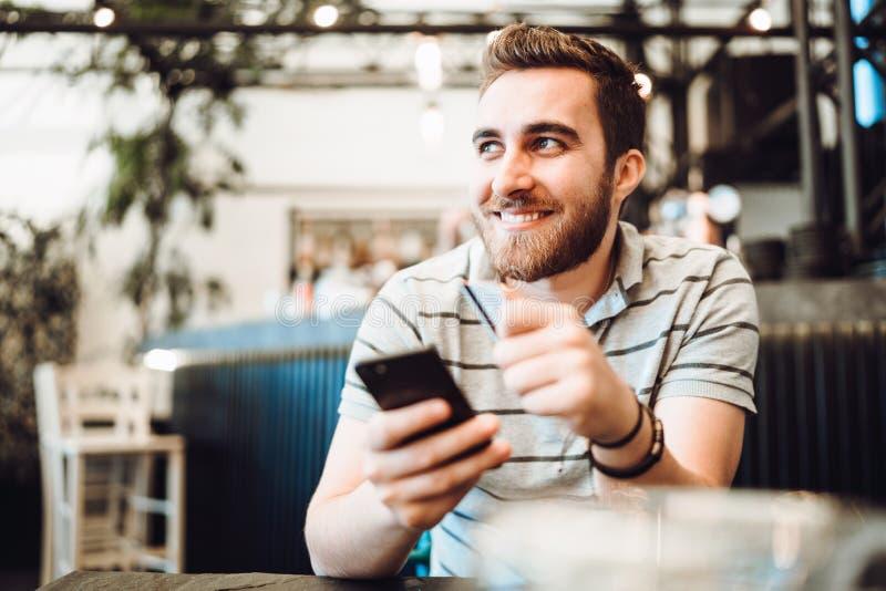 Uomo che paga facendo uso della carta di credito e del telefono cellulare Concetto di sistemi moderno di pagamento immagine stock libera da diritti