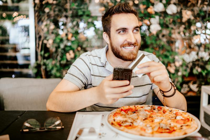 Uomo che paga la pizza facendo uso della carta di credito e del telefono cellulare Concetto di sistemi moderno di pagamento immagine stock