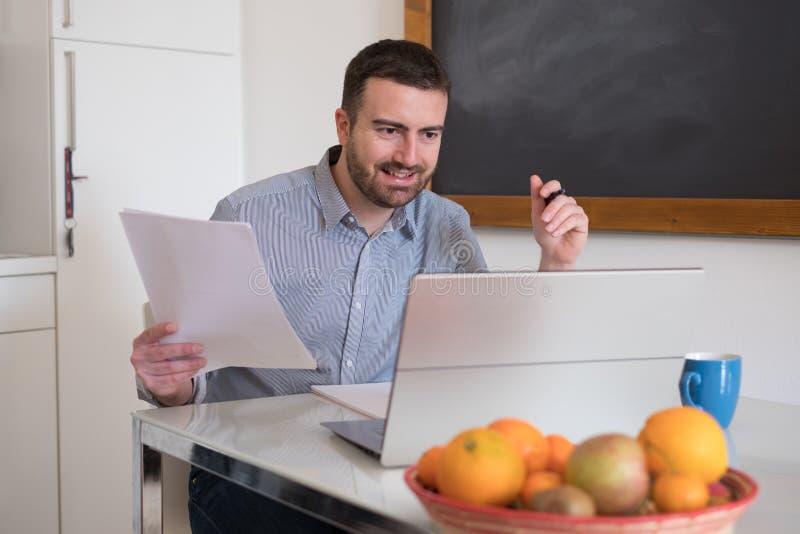 Uomo che paga le fatture facendo uso del servizio online di Internet fotografia stock