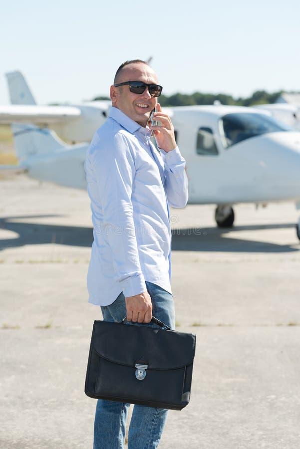 Uomo che parla sul telefono che cammina verso l'aeroplano privato immagini stock libere da diritti