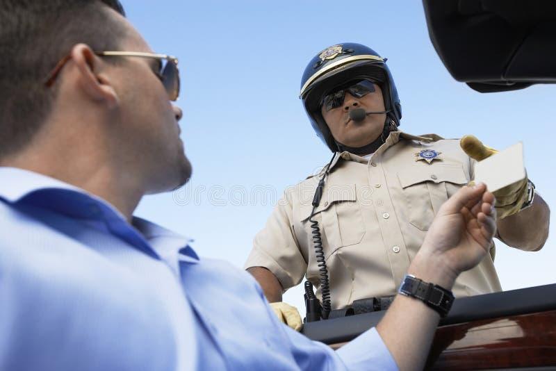 Uomo che passa licenza all'ufficiale di polizia immagini stock