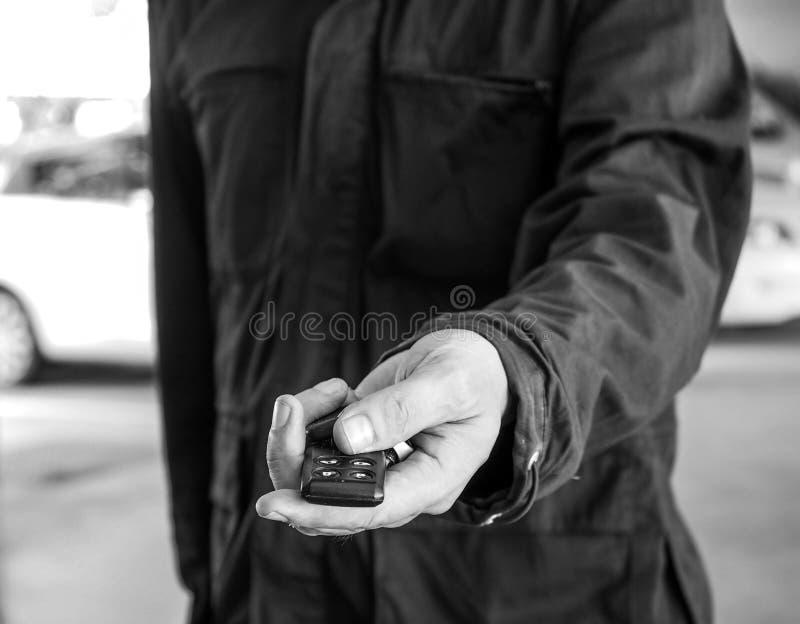Uomo che passa una chiave dell'automobile fotografia stock