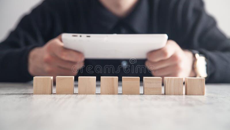 Uomo che per mezzo del calcolatore del ridurre in pani Cubi di legno nello scrittorio Tecnologia, affare immagini stock libere da diritti