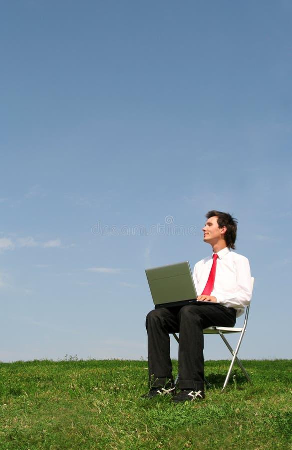 Uomo che per mezzo del computer portatile all'aperto fotografie stock