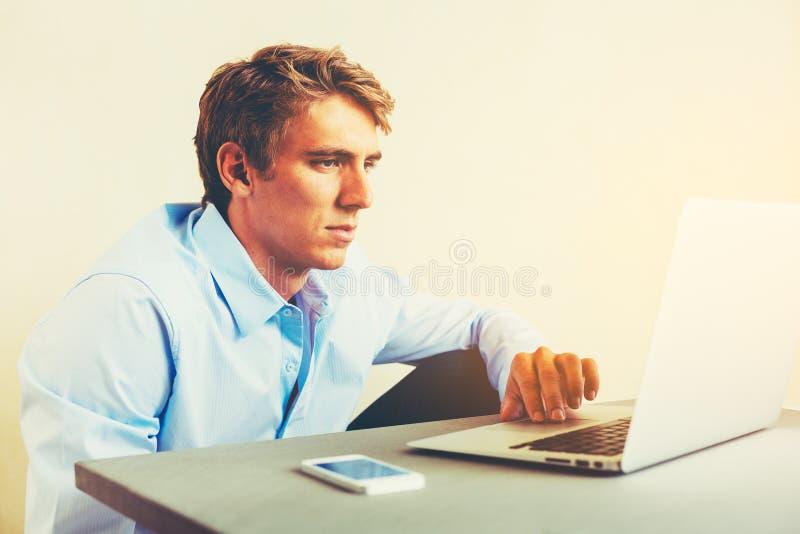 Uomo che per mezzo del computer portatile che funziona dalla casa immagine stock libera da diritti