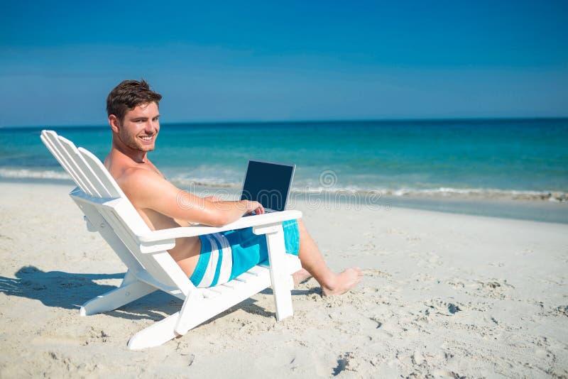Uomo che per mezzo del computer portatile su sdraio alla spiaggia immagine stock