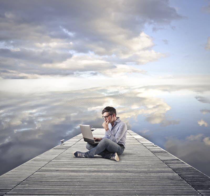 Uomo che per mezzo del suo computer portatile immagine stock