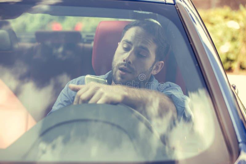Uomo che per mezzo del telefono cellulare che manda un sms mentre guidando Concetto del driver avventato fotografia stock libera da diritti