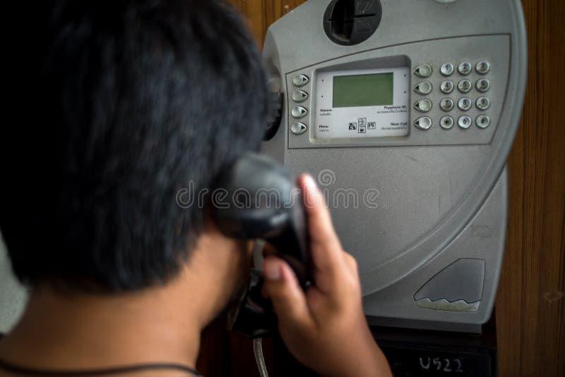 Uomo che per mezzo del telefono a gettone pubblico fotografia stock libera da diritti