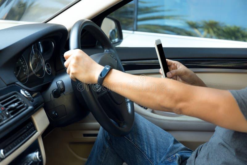 Uomo che per mezzo del telefono mentre conducendo l'automobile immagine stock libera da diritti